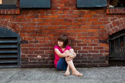 girl in front of bricks